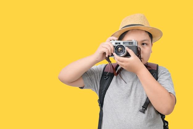 Menino obeso viajante tirando uma foto com uma câmera vintage