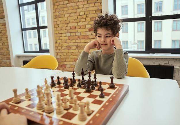 Menino observador sentado na sala de aula jogando xadrez no tabuleiro