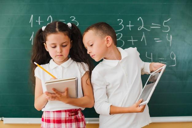Menino olhando no bloco de notas da menina
