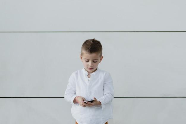 Menino olhando para baixo, brincando em seu telefone com uma parede branca