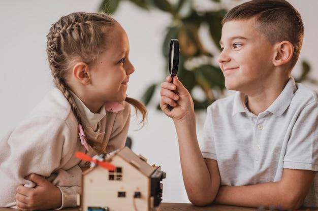 Menino olhando para uma menina com uma lupa