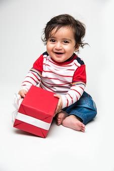 Menino ou bebê fofo indiano sorrindo com uma caixa de presente sobre fundo branco