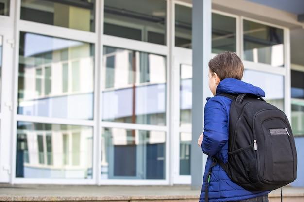 Menino ou criança em idade escolar indo para a escola, frequência escolar, conceito de educação