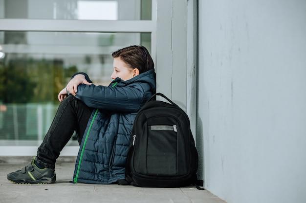 Menino ou criança sentada sozinha no chão em frente à escola após sofrer um ato de bullying