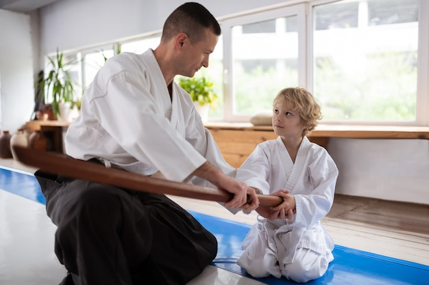 Menino ouvindo. garotinho loiro ouvindo seu professor de aikido sentado perto da janela