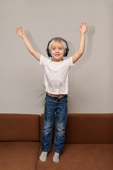 Menino ouvindo música e dançando com as mãos para cima
