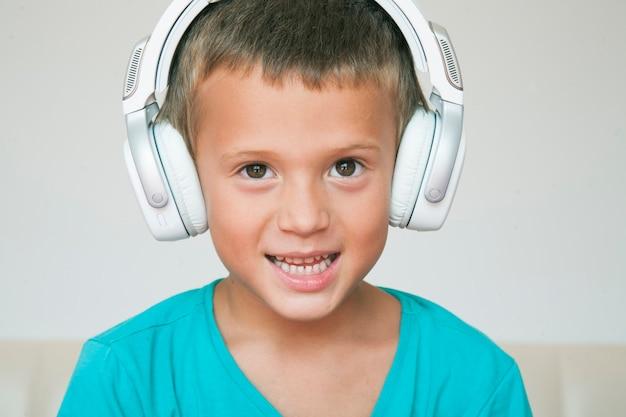 Menino ouvindo música em fones de ouvido.