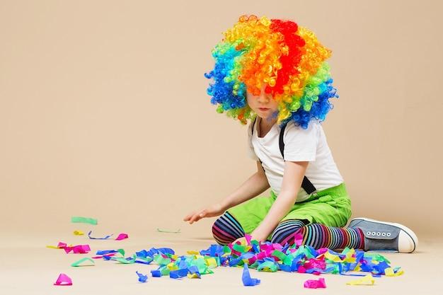 Menino palhaço feliz com uma grande peruca colorida