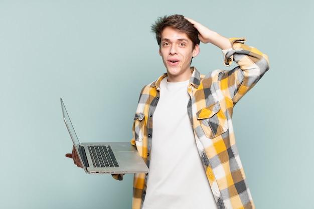 Menino parecendo feliz, espantado e surpreso, sorrindo e percebendo uma boa notícia incrível. conceito de laptop