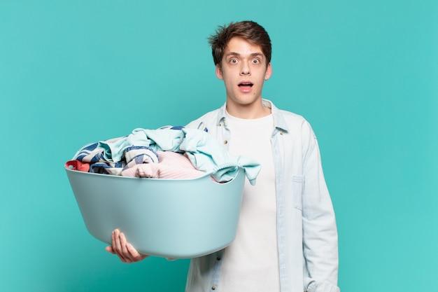 Menino parecendo muito chocado ou surpreso, olhando com a boca aberta dizendo uau, lavando roupa conceito