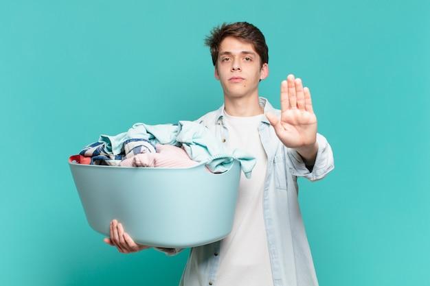 Menino parecendo sério, severo, descontente e irritado, mostrando a palma da mão aberta, fazendo gesto de parar de lavar roupa conceito