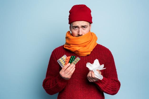 Menino pegou um resfriado e usa pílulas para curar. estúdio em fundo ciano