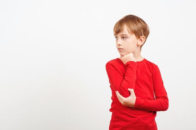 Menino pensando em pé isolado sobre fundo branco. olhando para o lado. criança pensativa desvia o olhar no espaço da cópia.