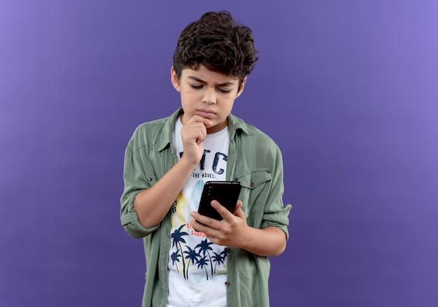 Menino pensando, segurando e olhando para o telefone isolado no roxo