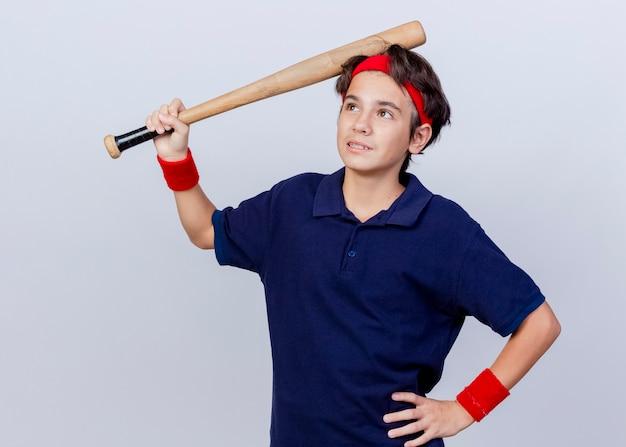Menino pensativo, bonito e esportivo usando fita para a cabeça e pulseiras com aparelho dentário, mantendo a mão na cintura, olhando para cima, tocando a cabeça com taco de beisebol isolado na parede branca