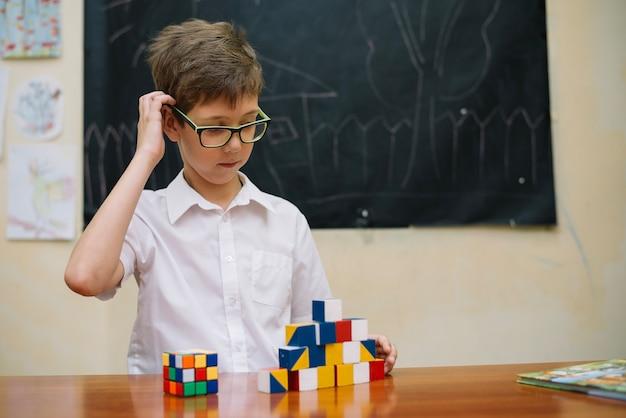 Menino pensativo com brinquedos de quebra-cabeça