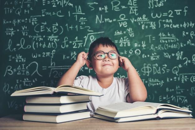 Menino pensativo com o livro na sala de aula