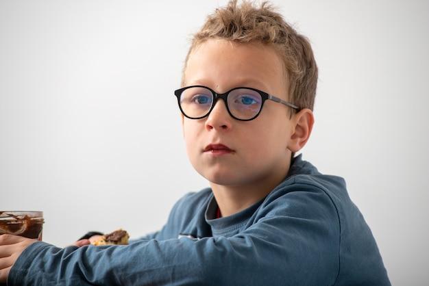 Menino pensativo com óculos, comer um chocolate