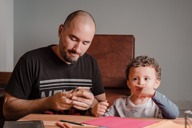 Menino pensativo com seu dever de casa enquanto o pai verifica o celular
