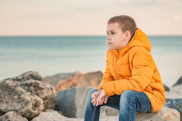 Menino pensativo com um casaco laranja à beira-mar ao pôr do sol. sonhos de criança. menino, mar, estilo de vida