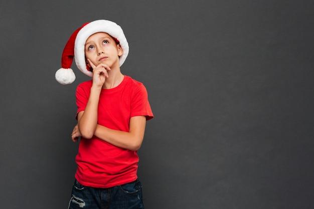 Menino pensativo criança usando chapéu de papai noel de natal