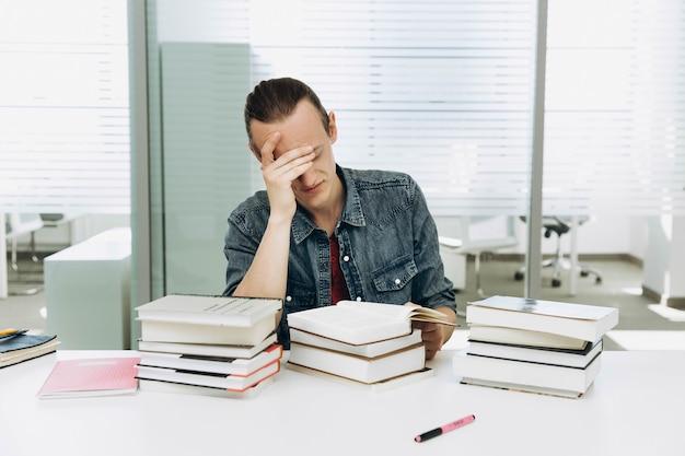 Menino pensativo e cansado trabalha com livros na biblioteca