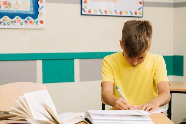 Menino pensativo escrevendo na aula