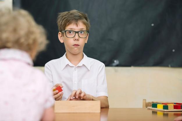 Menino pensativo na mesa com o jogo