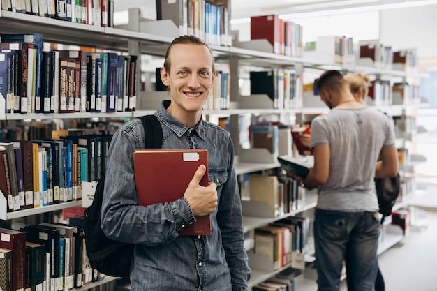 Menino pensativo parece um estudante de pé com livro na biblioteca de uma universidade