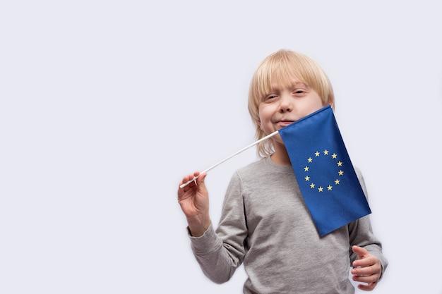 Menino pensativo segurando a bandeira da união europeia. educação na europa.