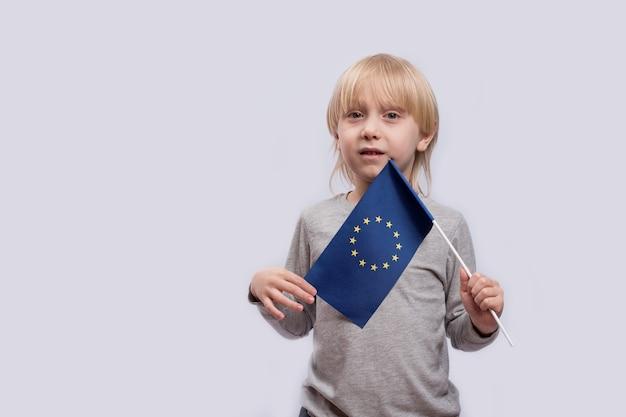 Menino pensativo segurando a bandeira da união europeia. viajar com crianças na europa.