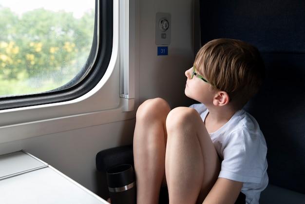 Menino pensativo sentado no vagão do compartimento e olhando pela janela
