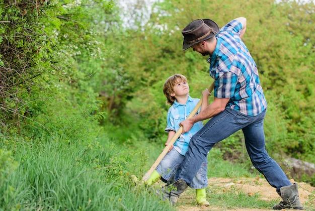 Menino pequeno ajuda o pai na agricultura. solo natural rico. fazenda ecológica. rancho. pai e filho plantando uma árvore genealógica. vida nova. fertilizantes de solos. feliz dia da terra. cave grounf com pá. plante no solo.