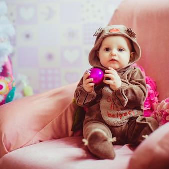 Menino pequeno alegre que joga perto da árvore de natal