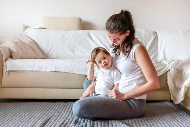 Menino pequeno bonito com síndrome de down, brincando com a mãe em casa