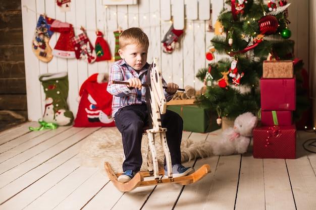 Menino pequeno, cavalo de balanço de madeira na frente da árvore de natal