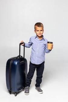 Menino pequeno com mala e xícara de café em pé isolado na parede branca