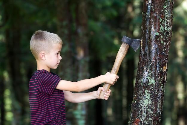 Menino pequeno com trunfo velho pesado da árvore do corte do machado do ferro na floresta no dia de verão. atividades ao ar livre e trabalho físico.