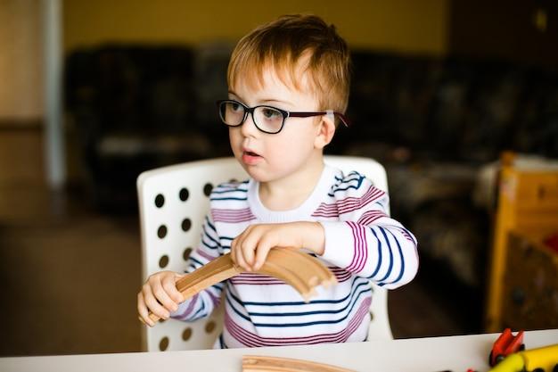 Menino pequeno da criança do gengibre nos vidros com alvorecer da síndrome que joga com estradas de ferro de madeira