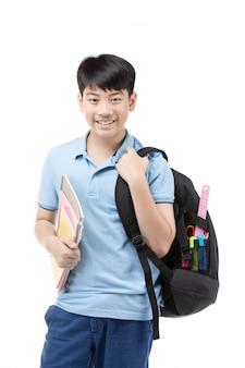 Menino pequeno de sorriso do estudante no t-shirt azul do polo dentro com livros e saco.