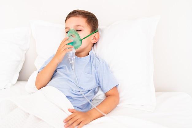 Menino pequeno deitado na cama doente com uma máscara para inalação