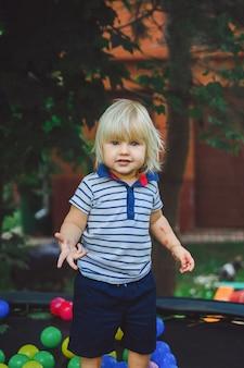 Menino pequeno em um trampolim com bolas coloridas