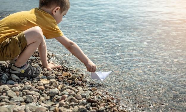 Menino pequeno está lançando um barco de papel branco na água do mar com fundo e costa pedregosos