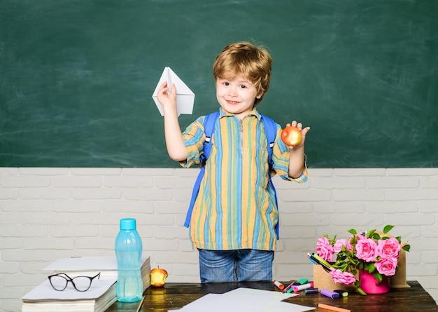 Menino pequeno estudante pintando na classe da escola melhor criança feliz da infância brincando com o avião de papel em