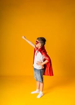Menino pequeno fantasiado de herói com uma máscara vermelha e uma capa em uma superfície amarela com espaço para texto