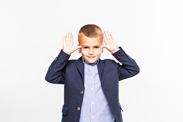 Menino pequeno faz divertido gesto isolado na parede branca