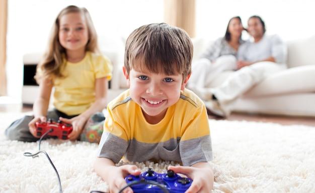 Menino pequeno jogando videogame com sua irmã