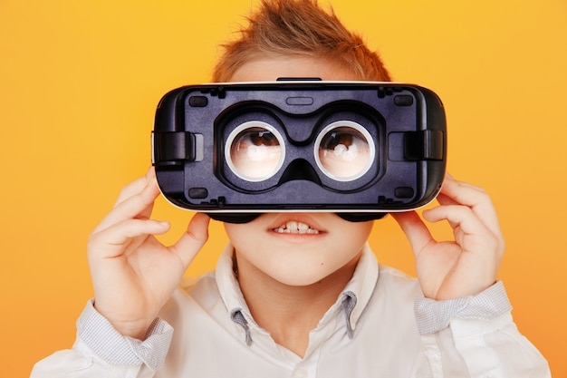 Menino pequeno na camisa branca, olhando para a câmera através do fone de ouvido da realidade virtual isolado