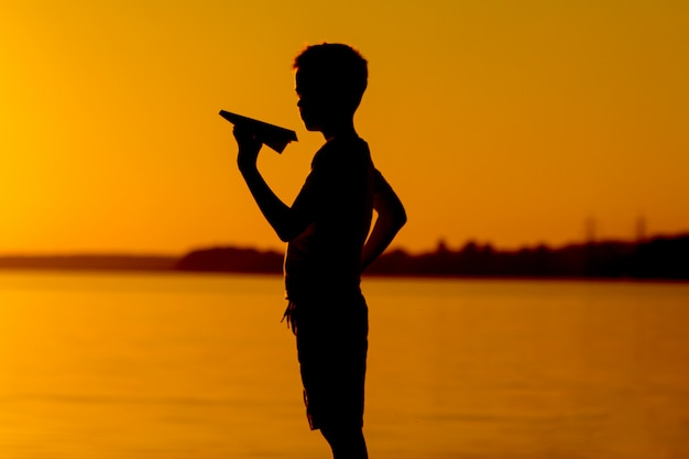 Menino pequeno tem um avião de papel na mão pelo rio no pôr do sol laranja no verão.