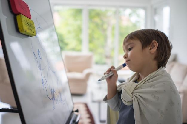 Menino pintando e desenhando a bordo em casa